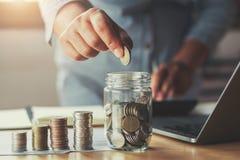 affärskvinnahand som sätter mynt i exponeringsglas för sparande pengar Conce arkivfoto