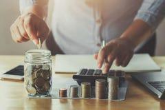 affärskvinnahand som sätter mynt i exponeringsglas för sparande pengar Conce royaltyfri foto
