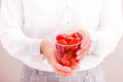 Affärskvinnainnehavkopp med nya små tomater royaltyfri fotografi