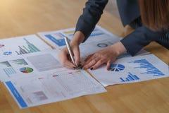 Affärskvinnainnehavpenna som pekar på affärsdokument till analysbruk för att plan ska förbättra kvalitet på mötesrum royaltyfria foton