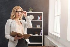 Affärskvinnaläsebok på kontorsskrivbordet fotografering för bildbyråer