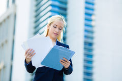 Affärskvinnaläsning som granskar företagsdokument Royaltyfria Bilder
