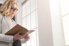 Affärskvinnaläsningdokument på kontorsskrivbordet arkivfoton