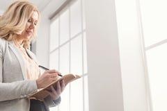 Affärskvinnaläsningdokument på kontorsskrivbordet royaltyfria bilder