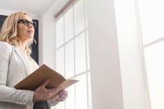 Affärskvinnaläsningdokument på kontorsskrivbordet arkivbild