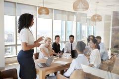 AffärskvinnaLeads Meeting Around tabell som skjutas till och med dörr royaltyfri foto