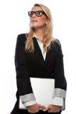 AffärskvinnaLooking Up While hållande bärbar dator royaltyfri fotografi