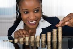 AffärskvinnaMaking Stack Of mynt arkivbild