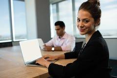 Affärskvinnamaskinskrivning på bärbara datorn på tabellen med den manliga kollegan i bakgrund Royaltyfria Bilder