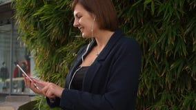 Affärskvinnamaskinskrivningmeddelandet och att lyssna till musik utanför med slut vänder mot upp lager videofilmer