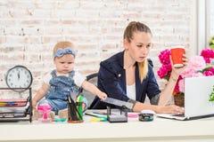 Affärskvinnamoderkvinna med en dotter som arbetar på bärbara datorn arkivbild