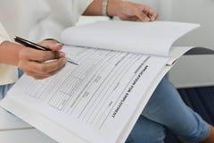 Affärskvinnan är fyller upp ansökningsblanketten Fotografering för Bildbyråer