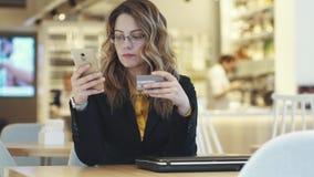 Affärskvinnan överför ett kreditkortnummer en flicka i en affärsdräkt begår ett online-köp lager videofilmer