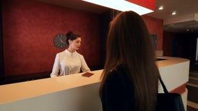 Affärskvinnan ankommer till hotellet på mottagandet och får en tangent 4K stock video