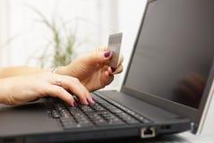 Affärskvinnan använder bärbara datorn för på linjen betalning med kreditering ca Royaltyfri Bild