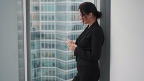 Affärskvinnan använder en mobiltelefon, medan stå på fönstret av en skyskrapa arkivfilmer