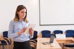 Affärskvinnan använder hennes minnestavla i kontoret Royaltyfri Bild
