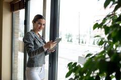 Affärskvinnan bredvid fönster använder minnestavlan Arkivfoto