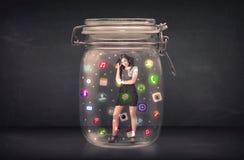 Affärskvinnan fångade i en glass krus med färgglade app-symboler c Arkivbilder