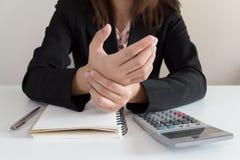Affärskvinnan får smärtar handen, medan arbeta i hans kontor royaltyfria bilder