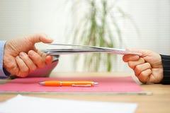 Affärskvinnan ger coworkeren post- lettersin postläsningen Fotografering för Bildbyråer