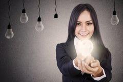 Affärskvinnan ger ljus idé Arkivfoto