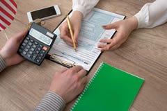 Affärskvinnan granskar formen för skatt 1040 Royaltyfri Fotografi