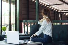 Affärskvinnan har den stränga skuldran att smärta, begreppet av sjukdomen från arkivbild