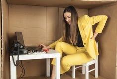 Affärskvinnan har tillbaka att smärta från arbete i ett litet kontor Arkivfoto