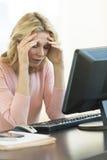 Affärskvinnan With Head In räcker sammanträde på skrivbordet royaltyfri fotografi
