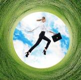 Affärskvinnan hoppar i roterande fält med grönt gräs Arkivfoton