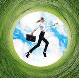 Affärskvinnan hoppar i roterande fält med grönt gräs Royaltyfri Bild
