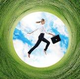 Affärskvinnan hoppar i roterande fält med grönt gräs Royaltyfri Foto