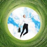Affärskvinnan hoppar i roterande fält med grönt gräs Arkivbild