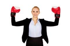 Affärskvinnan i boxninghandskar som står i seger, poserar arkivfoto