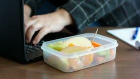 Affärskvinnan i dräkt har arbete på bärbara datorn och att äta ett fruktmellanmål från lunchasken arkivfilmer