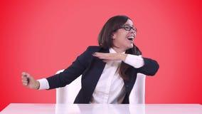 Affärskvinnan i ett sammanträde för affärsdräkt bak ett skrivbord och tycker om en hel del Röd bakgrund lager videofilmer