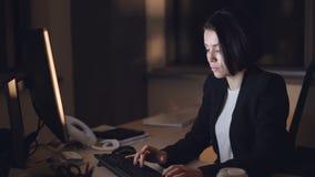 Affärskvinnan i formell dräkt arbetar på datornattförskjutningen som sitter på skrivbordet som skriver och ser skärmen Upptaget u stock video
