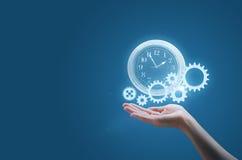 Affärskvinnan i gömma i handflatan av din hand håller klockan, och kugghjulen symboliserar processen av en lyckad affär arkivbild