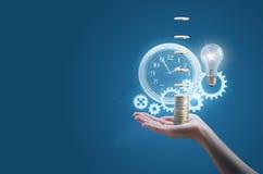 Affärskvinnan i handen av en klocka utrustar pengar, och lampan symboliserar det effektiva genomförandet Arkivfoton
