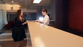 Affärskvinnan kommer till hotellet som in kontrollerar på ett mottagandeskrivbord 4K stock video