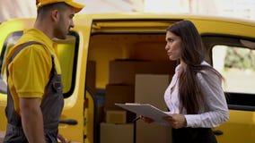 Affärskvinnan kontrollerar leverans från kurir i den gula likformign som är utomhus- nära hans bil lager videofilmer