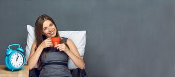 Affärskvinnan kopplar av i regeringsställning med kaffekoppen royaltyfri foto