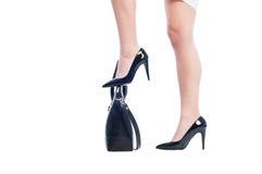 Affärskvinnan lägger benen på ryggen att kliva på handväskan eller handväskan Royaltyfri Foto