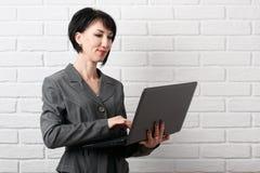Affärskvinnan med bärbara datorn som är iklädd en grå dräkt, poserar framme av en vit vägg Arkivfoto