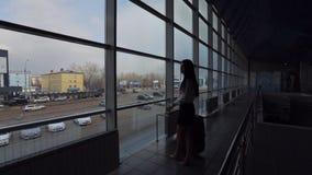 Affärskvinnan med bagage står near fönster i flygplats lager videofilmer