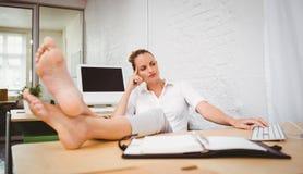 Affärskvinnan med ben korsade på ankeln på skrivbordet Royaltyfria Bilder