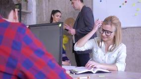Affärskvinnan med exponeringsglas som sitter på skrivbordhandstil, noterar i en anteckningsbok och limmar kulöra klistermärkear p arkivfilmer