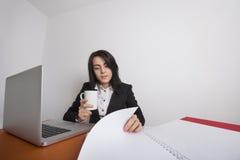 Affärskvinnan med kaffe rånar läsningdokument på skrivbordet i regeringsställning Royaltyfri Foto