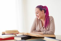 Affärskvinnan med rosa hår sitter i kontoret läser bokutbildning royaltyfri fotografi